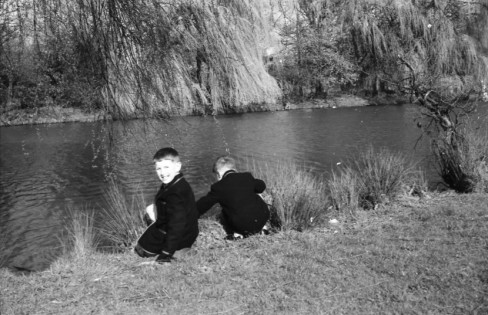 Black and white photograph of Roger and his brother playing in the brook at Markeaton Park.