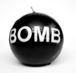 Black candle with 'bomb' written in white on the front.