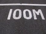 Image '100M' in white paint on the track at Normanton Park.